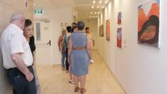 """מבקרים בתערוכה מתבוננים ביצירותיו של ד""""ר אמי שופמן"""