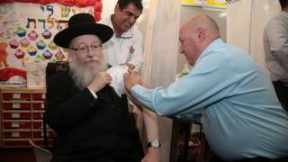 פרופ' איתמר גרוטו (מימין) מזריק את החיסון לשפעת לשר הבריאות, יעקב ליצמן (צילום: משרד הבריאות)