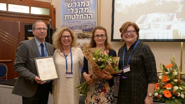 """ד""""ר חני ישועה (במרכז, עם הפרחים) מקבלת את פרס המומחה הוותיק המצטיין בכנס האיגוד לרפואת משפחה (צילום: יח""""צ)"""